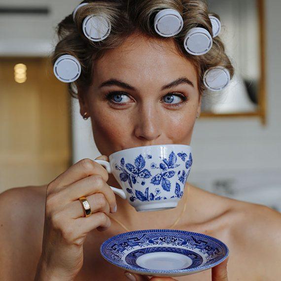 Bruid drinkt kopje thee terwijl haar haar in de krul zit